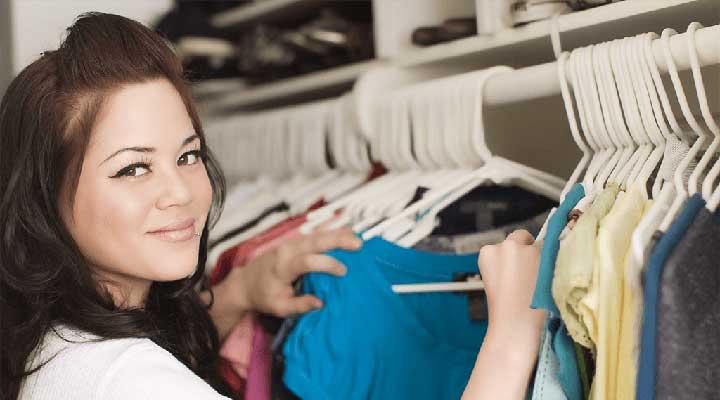 smiling woman looking through clothes in her closet