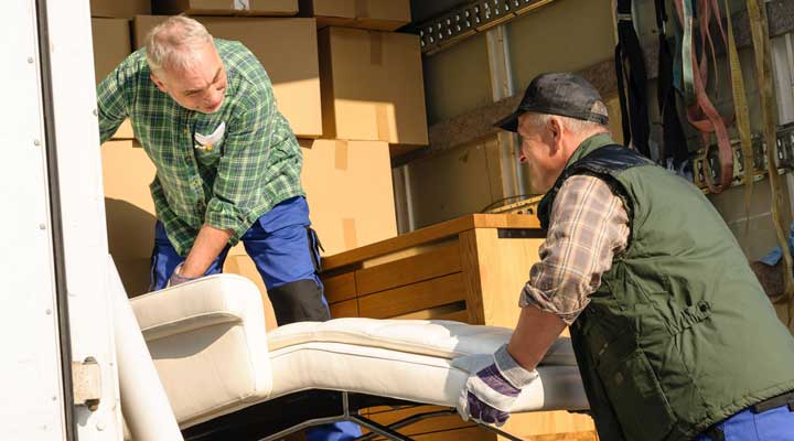 two men move furniture into a moving truck