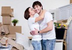 couple surrounded by moving boxes and furniture the woman is kissing the man on the cheek 145x100