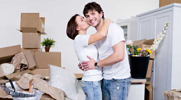 couple surrounded by moving boxes and furniture the woman is kissing the man on the cheek