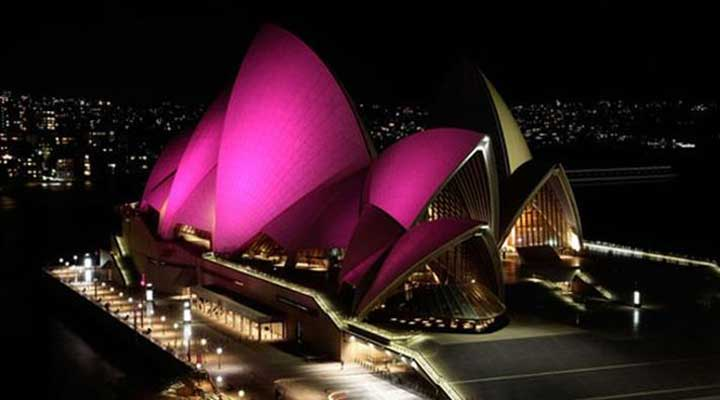 sydney opera house illuminated with pink light