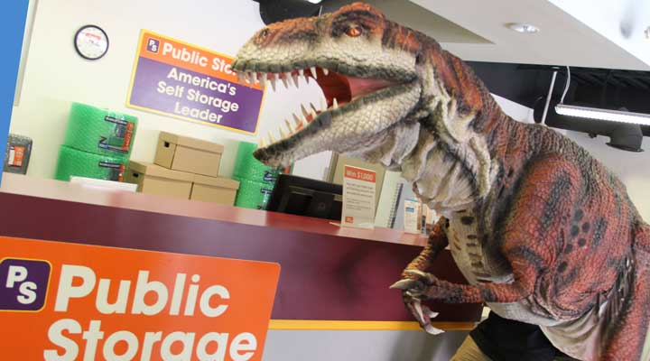 people in kojo the dinosaur costume at a public storage office counter