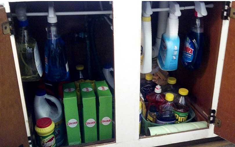 cleaning supplies hanging on a tension rod in an under sink cabinet