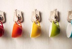 colorful coffee cups hanging from hooks on a wall 145x100