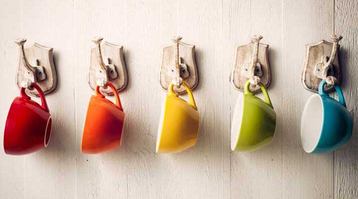colorful coffee cups hanging from hooks on a wall