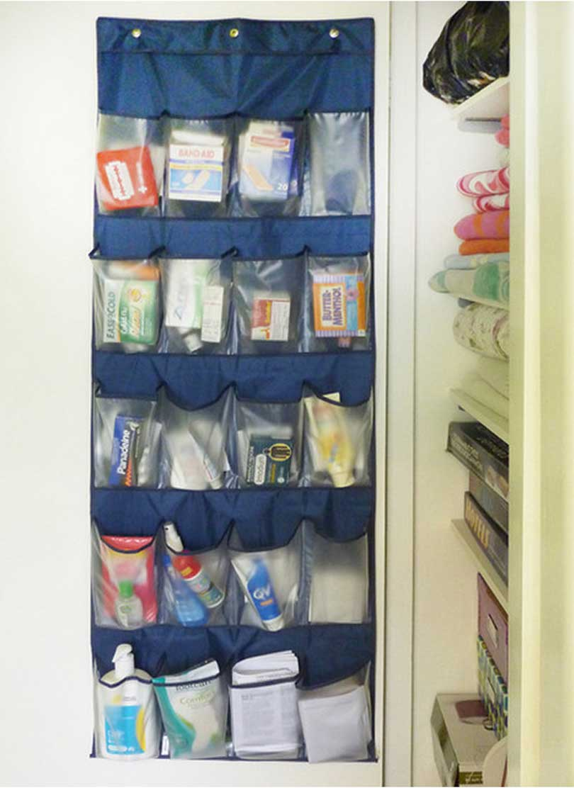 fabric shoe organizer on the back of a hall closet door stores medicine cabinet items