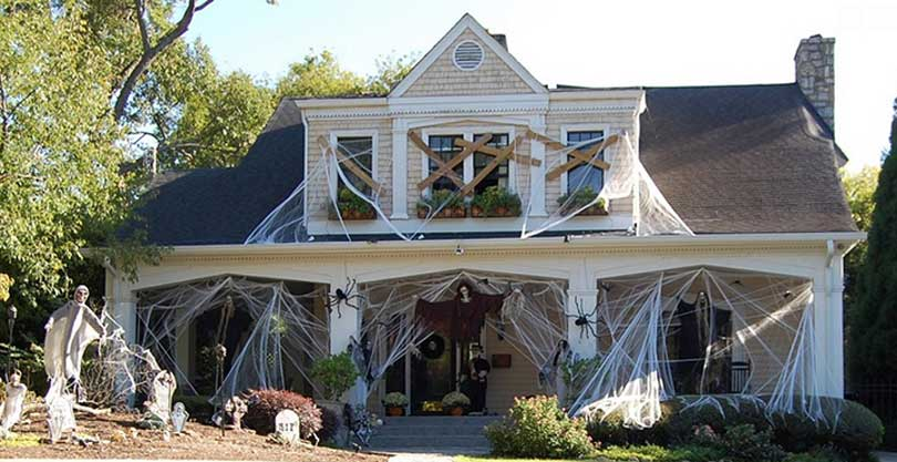 haunted house covered in cobwebs and boarded up