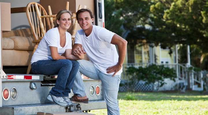 couple posed outside their moving truck