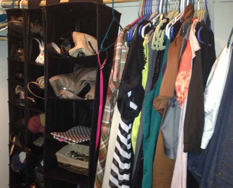 hanging sweater organizer in closet storing purses and other accessories