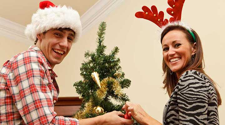 smiling couple decorates a christmas tree