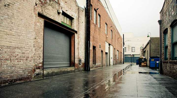 industrial alley with a roll down storage door in a building in the rain