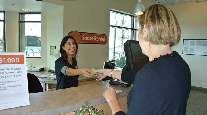 public storage customer paying her bill to an employee at a storage facility office