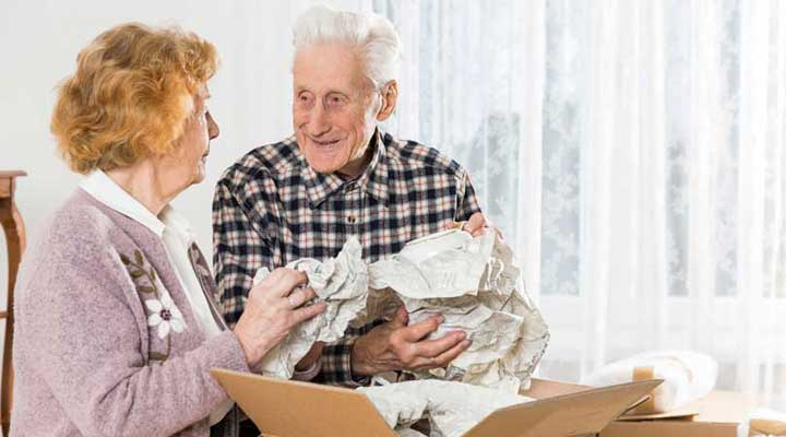 senior couple packing a box together for a move to downsize