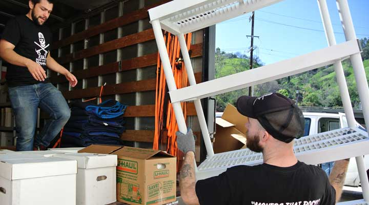 movers load a truck with furniture