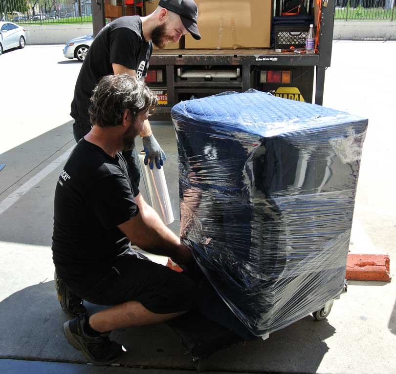 movers wrap furniture in blankets and plastic