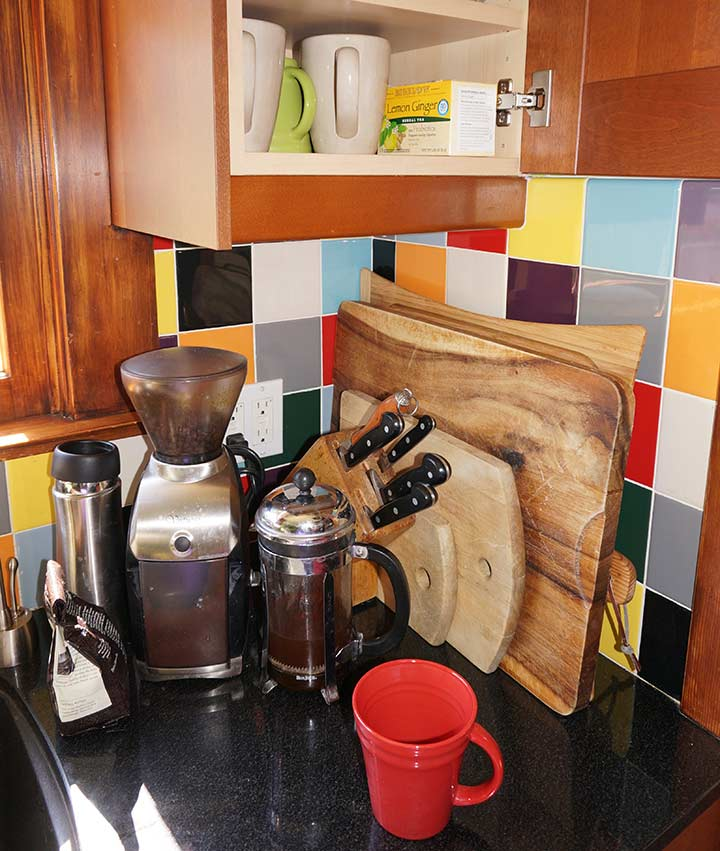 coffee station set up in a kitchen corner with mugs and maker stored nearby