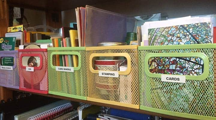 shelf with colorful wire bins labled with different types of craft supplies such as cards stamping