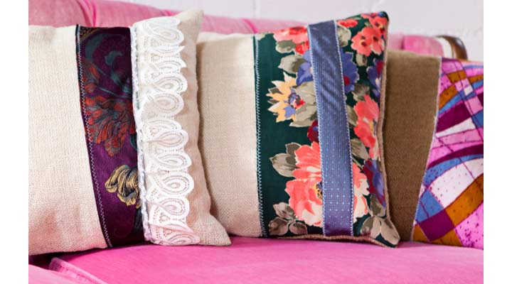 very colorful patchwork pillows adorn the vintage pink couch