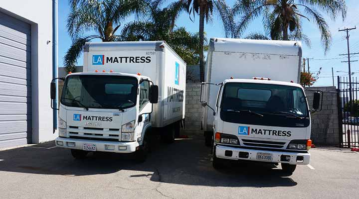two mattress movers trucks parked