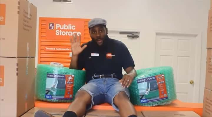 public storage employee sitting next to rolls of bubblewrap