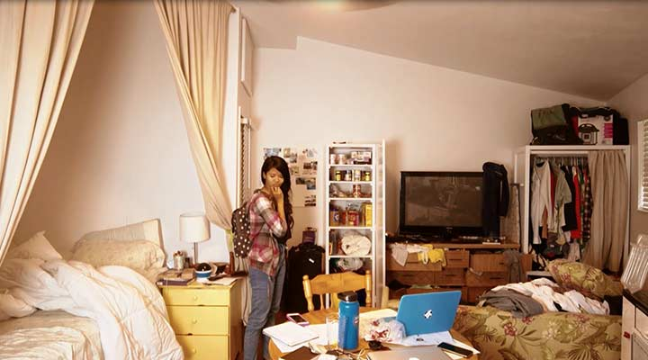 pensive woman standing in the middle of cluttered room