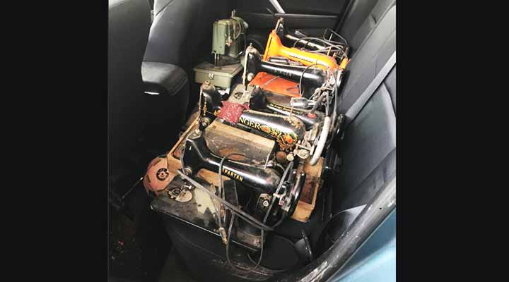 vintage sewing machines in the backseat of a car