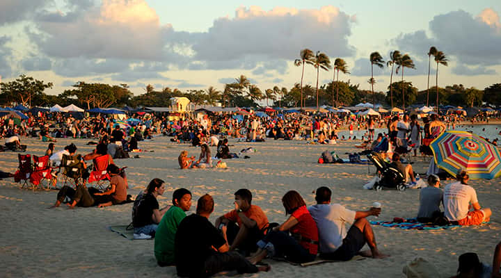 crowded Hawaii beach near sunset