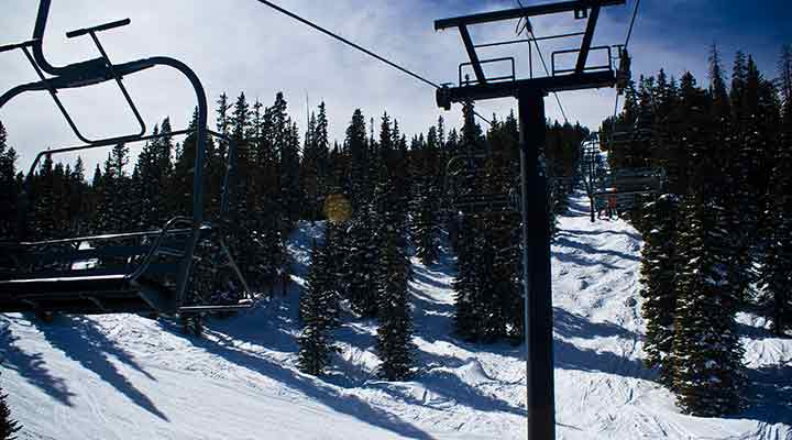 chair lifts heading up snowy mountain