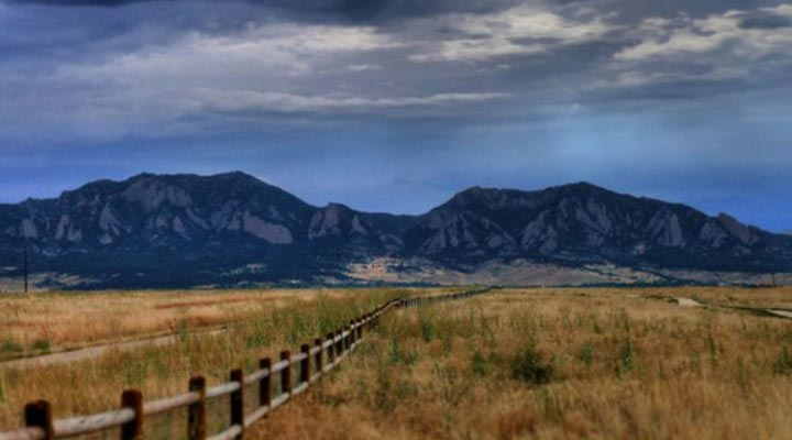 view of a fenceline with the flatirons in the background