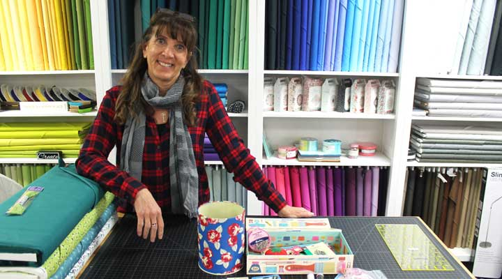 julia marquez of sewing arts stand in front of fabric supplies