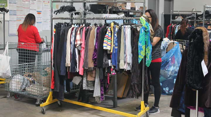 Goodwill Los Angeles workers prepping clothing racks
