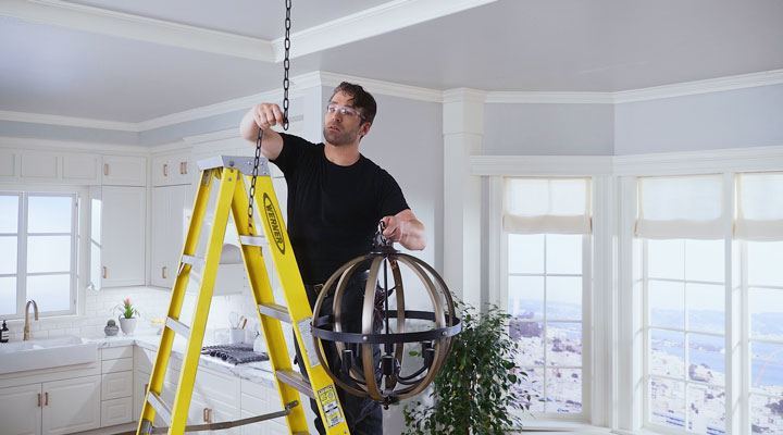 man stands on ladder hanging chandelier to chain