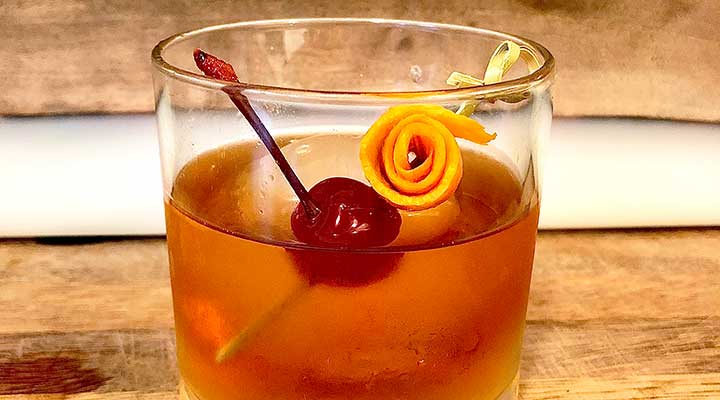 closeup of an old-fashioned with a cherry and orange peel in a pick
