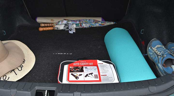 Organized car trunk with emergency kit yoga mat and spare shoes and hats