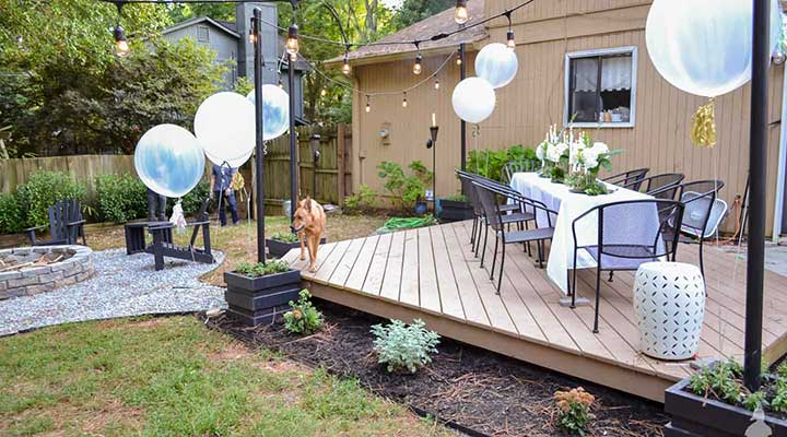 Outdoor of a tan wood deck with a diy planter poles with string lights