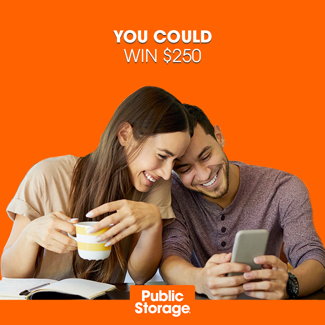 young couple sitting next to each other looking at Public Storage YouTube contest on their cell phone