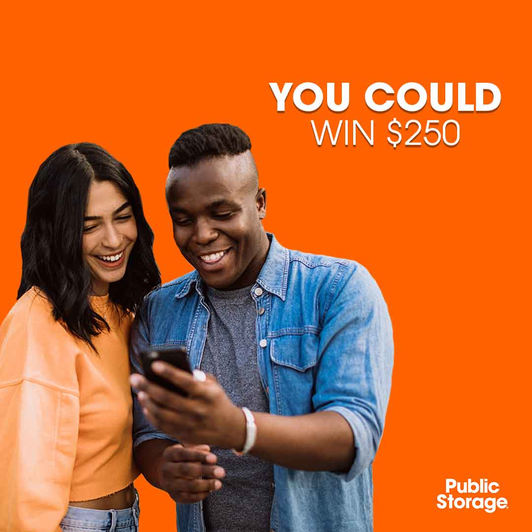 young woman and man looking at YouTube comment contest on cell phone with orange backdrop