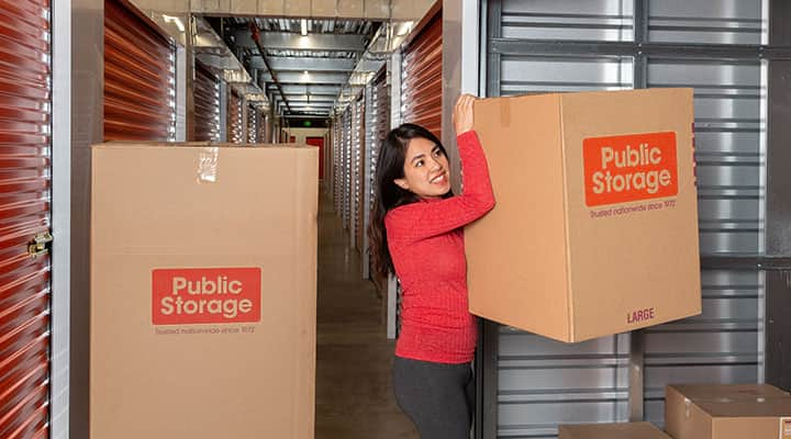 Woman wearing red shirt moving public storage boxes using contactless erental service