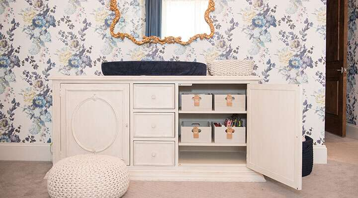 A room with an elegant white dresser and baby changing station with a blue floral wallpaper backdrop