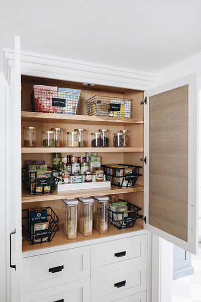 White organized pantry filled with food