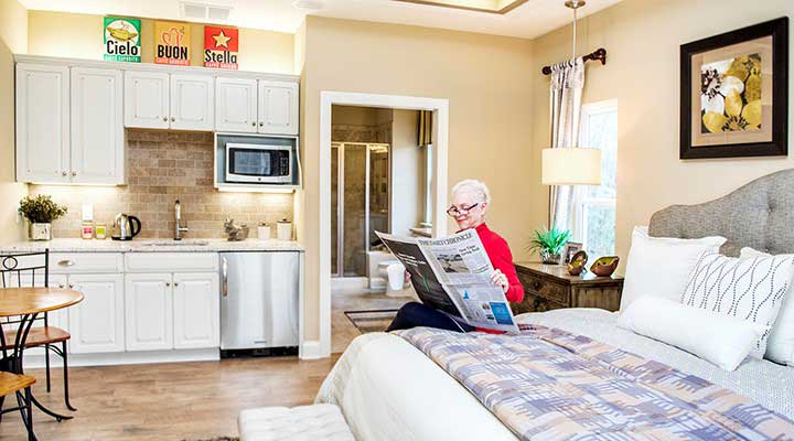 Grandma reading newspaper in a Schumacher Homes multigenerational home floor plan