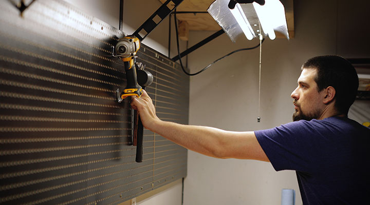 Young man standing in front of black pegboard storage wall hanging up tools in garage
