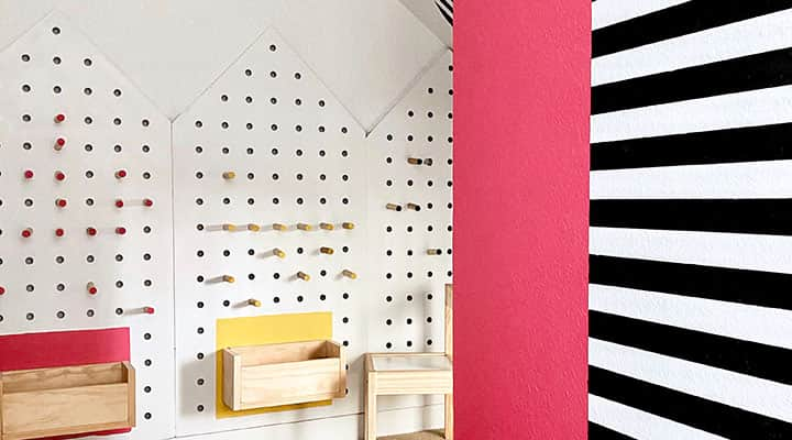 White DIY Pegboard shaped houses under staircase space with black and white stripe accent wall