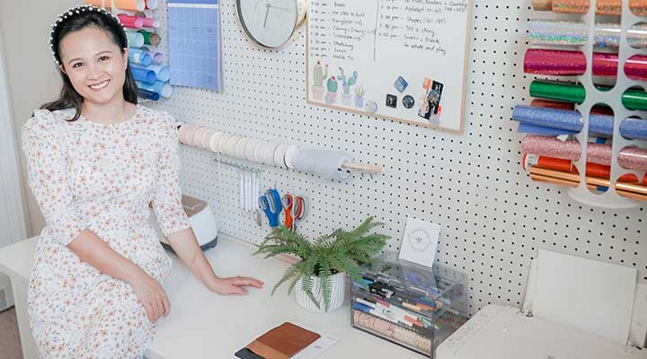 Young woman sitting on a white table in front of a DIY pegboard storage wall