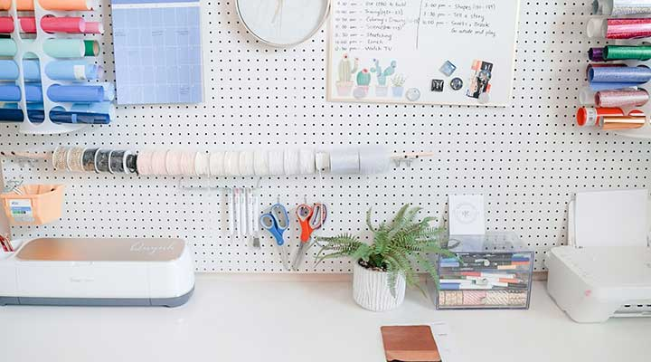 Closeup of white craft room DIY pegboard storage wall