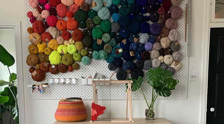 Ikea Skadis pegboard storage panels used for yarn wall in a home