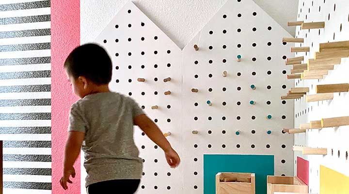 Toddler runs past toy storage pegboard walls