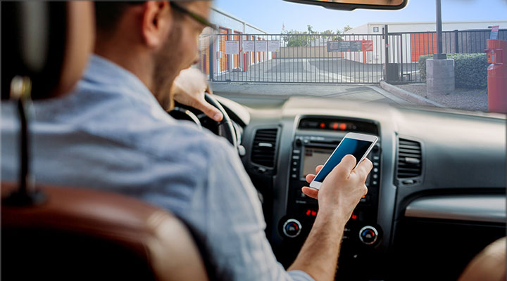 guy in a car opening gate with Public Storage app