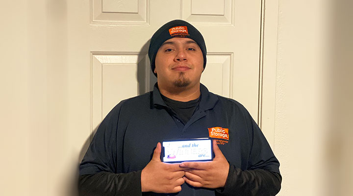 public storage property manager holds up phone announcing winners of virtual fitness challenge
