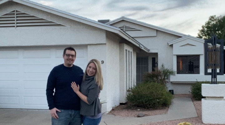 first time buyer couple standing in front of phoenix home